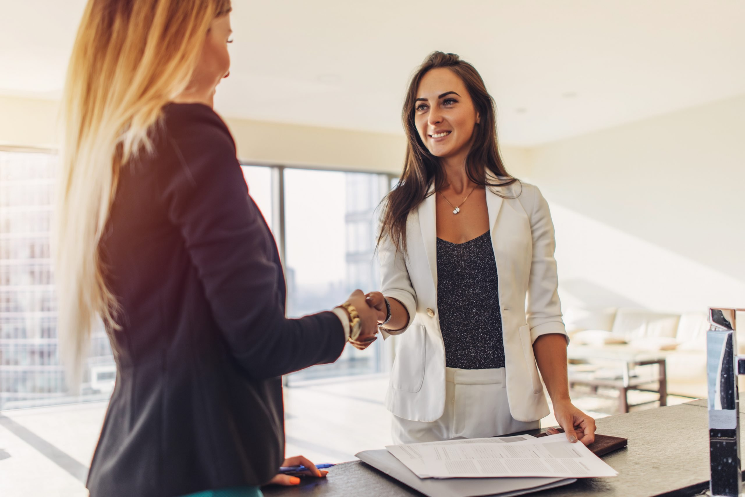 Female customer shaking hands with real estate agent agreeing to sign a contract standing in new modern studio apartment.